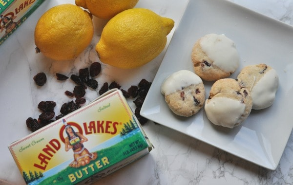 Easy recipe to make White Chocolate Cranberry Cookies. A buttery shortbread cookie with pops of lemon and cranberry and then dipped in white chocolate. http://diningwithalice.com/desserts/white-chocolate-cranberry-cookies/