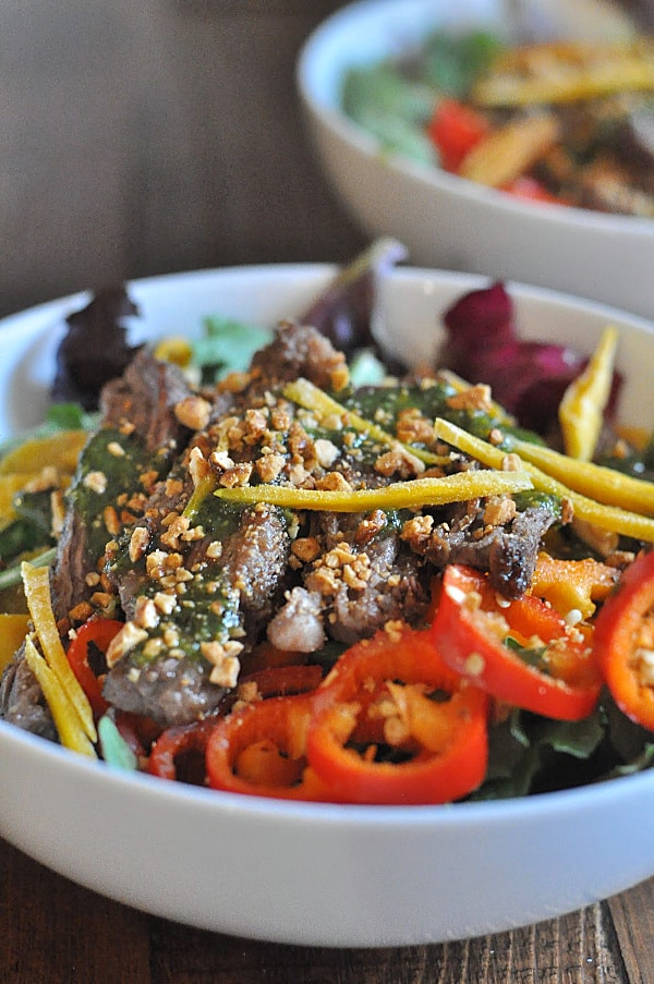 A bowl of Thai Steak Salad made with seasoned grilled Skirt Steak, a sweet cilantro sauce, and tossed with mango, peppers, honey peanuts, fresh mint, and your favorite mixed greens!