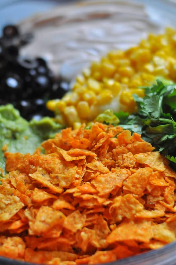 This easy Taco Salad is a quick recipe and is layered with Doritos, ground beef and your favorite taco toppings like corn, cilantro, Nacho Cheese doritos, guacamole, tomatoes, sour cream.