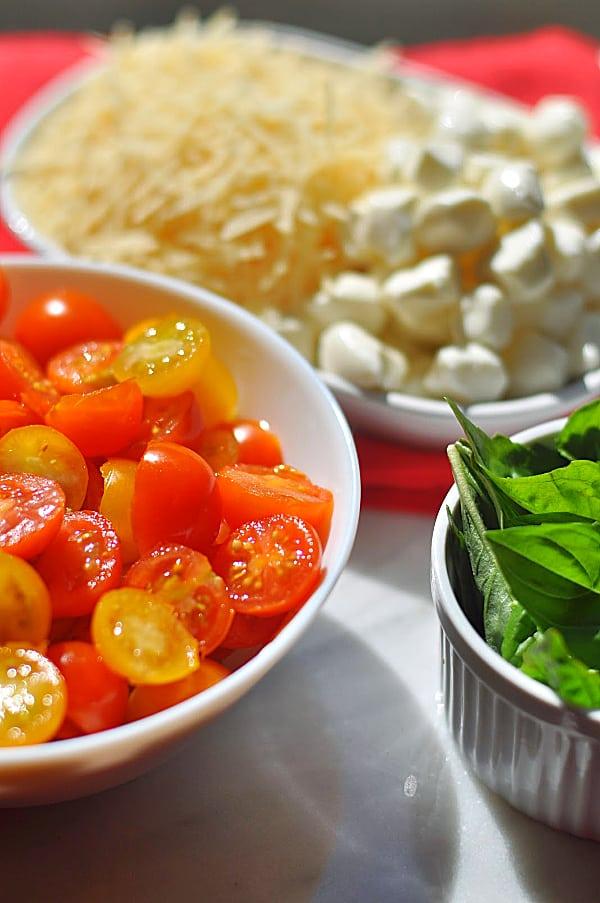 Caprese pasta salad ingredients of mozzarella, tomatoes, and basil.