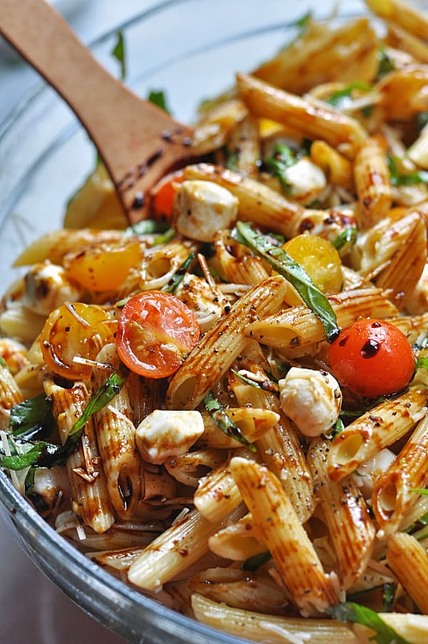 This Caprese pasta salad recipe is an easy make-ahead dish for weeknight dinner or potlucks. Made with basil, mozzarella, tomatoes, and balsamic glaze.Bowl of caprese pasta salad with fresh basil.