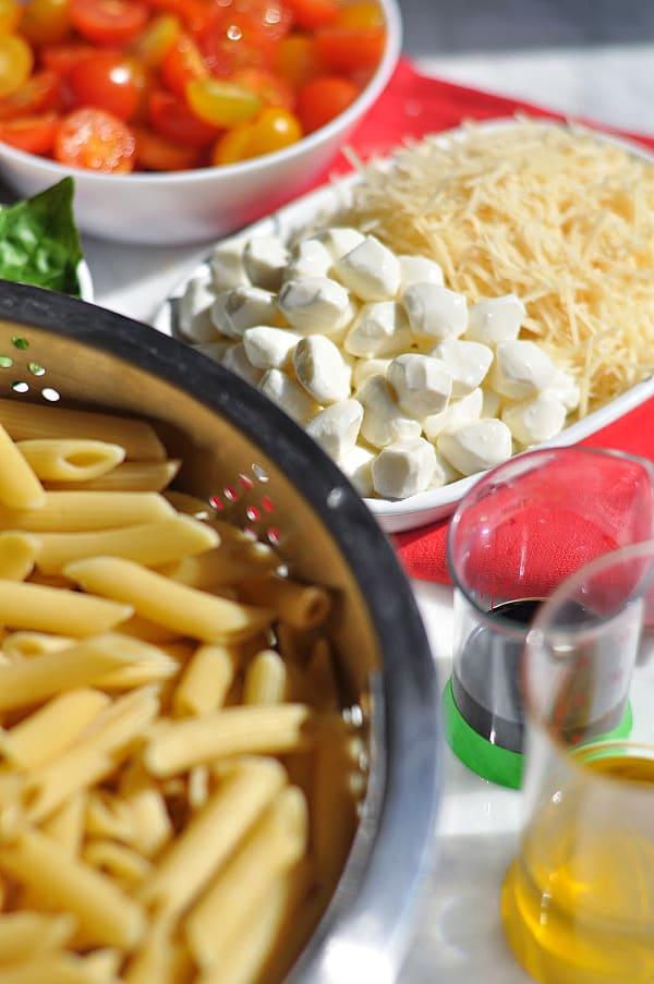 Caprese pasta salad ingredients of mozzarella, pasta, and balsamic glaze.